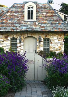 slate tile roof, stone facade and that greige paint on the door, trim and gate with the deep purple bushes - love