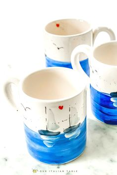 Bring a splash of color to your morning coffee, afternoon tea, or evening hot toddy (we won't tell). These ceramic sailboat mugs are lovingly handpainted by an artisan in Italy. Inspired by the Ionian seaside towns in Sicily, you'll have a bit of Italian charm in your daily routine. #sailboatmug #coffeemug #sailboatcoffeemug #seadecor #beachdecor #sailboatdecor #sailboat #handpainted #handpaintedceramics #artisanmade #madeinitaly #seadecor #oceandecor #coastaldecor #nautical #nauticaldecor