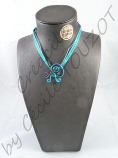 Pendentif en fil aluminium gaufré bleu turquoise et noir.   Composé d'un tour de cou en rubans assortis.   Ce bijou simple et discret ajoutera une touche de fantaisie à vos tenues sobres et chics.   Ses courbes généreuses le rende féminin à souhait.   Il s'accordera merveilleusement aux yeux bleus !