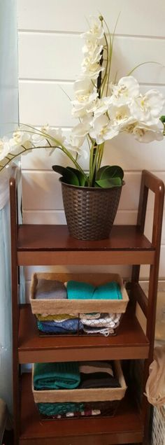 Another ladder shelf used for decor. Wire Baskets from the dollar store are used to hold wash cloths for a simple look with a little color.