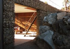 Volcanic stone gabions support meditation platform at Utah spiritual retreat Gabion Cages, Gabion Wall, Buddhist Retreat, Volcanic Rock, House On The Rock, Exterior Siding, House Wall, Patio Roof, Residential Architecture