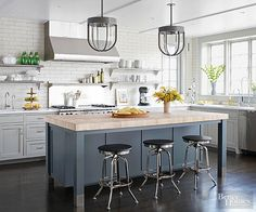 Inspired by a favorite restaurant, this family kitchen stretches out to become a hip, industrial-style hangout. Pale gray perimeter cabinets, a deeper blue-gray island, and steel shelves flank the range while delivering a bistro-like vibe. The kitchen's large scale allowed the homeowners to forgo hanging cabinets for sleek metal shelves while also reorienting the island.