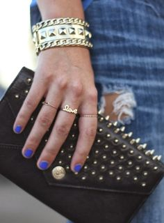 "Wide, gold bangle, gold ""love"" ring, and a black handbag with gold spikes."