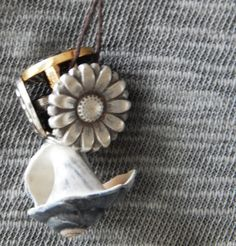 This necklace was made from a foraged conch shell found on the Outer Banks of North Carolina. It also features vintage buttons, all gathered on