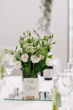 Simple elegant square vase of white lisianthus and greenery for wedding reception.