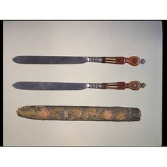 Pair of wedding knives V&A M.12 to B-1950; dated to 1638;  The finial of the octagonal handle is silver filigree, above convex drop-shaped clear amber panel over a white amber profile bust of a man, set against foil. In the central section clear amber panels over painted foil alternate with ivory strips. The foil is decorated with designs of coursing dogs and other animals.