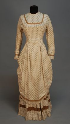 1880's printed cotton polonaise. Cream with repeat of brown grape clusters, unboned pannier bodice with pleated ruffle to yoke and cuff, brown trim bands, back buttons, lace hem trim, under skirt with double row of hem pleats.