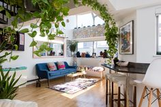 The vibrant living room is the focal point of their apartment; they were immediately drawn to how suddenly the space opens up into a lofty atrium and wanted to deliver a colorful first impression. They do so with found goods from nature and art created by their closest friends. They've also got a team of philodendrons filling out the white space on the walls, creating the illusion of an ivy jungle.