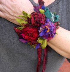 little recycled silk cuff wild scrappy raggy earthy raw! adorned with hand crocheted silk roses. in colours of burgundy, deep red, purple, pink, a little green, and some metallic glittery threads. modelled on a 7 1/2 inch wrist lace up - with silk ties, size adjustable - can easily be made larger or smaller please contact me if you have any questions thanks for visiting! Rosemary