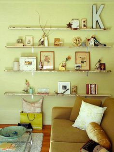 A wonderful way to add personality to a room: Narrow weathered planks act as display ledges and conserve space in a small living room. An arrangement of figurines, artwork, and found objects in a variety of shapes and sizes adds interest to the living room.