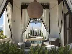 Mediterranean patio features doorways dressed in black and white outdoor curtains as well as Moroccan lantern illuminating sitting area composed of outdoor chairs and gray outdoor poufs next to in ground pool. Outdoor Curtains For Patio, Outdoor Pouf, Outdoor Rooms, Outdoor Chairs, Outdoor Living, Deck Patio, Backyard, Beach House Tour, Beach Houses