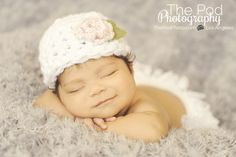 Newborn girl with hat and bloomers on gray floral fabric to infinity www.ThePodPhoto.com