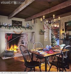 Christmas: open hearth fireplace, typical of the colonial style graces eating area open to ktchen, four black windsor style chairs echo the style