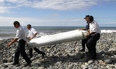 Officers carrying debris from an as-yet unidentified aircraft thought to be MH370 washed ashore in Saint-Andre de la Réunion last week.