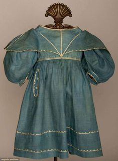 "Toddler's Summer Dress, c1830;  Fine indigo dyed linen, white linen braid, attached wide collar over gigot sleeve, 4 button faux pockets, linen lined bodice, W 19"", L 22"""
