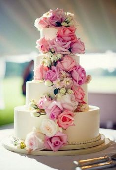 four tier white wedding cake with gorgeous pink roses wrapped around