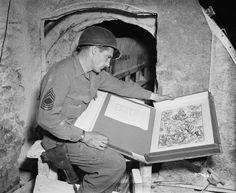 April 13, 1945, Sgt. Major Harold Maus examines an Albrecht Dürer engraving, found among other art treasures in a salt mine in Merker, Germany.
