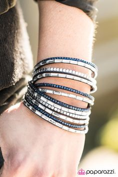 A band of blue suede is spliced into six glistening strands and decorated with blue rhinestones, glassy emerald-cut gems, and flat silver cube beads. The elongated design allows for a trendy double wrap around the wrist. Features an adjustable snap closure.   Sold as one individual bracelet.