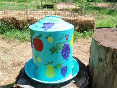 """This is a chicken water bucket that rusted out in the bottom tray. I painted with marine paint and then painted on some summer fruits. I use it for a wonderful """"WINE BOTTLE BUCKET""""!! Slide on lid to keep cool water drains out bottom into ring and dribles out on ground.."""