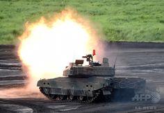 静岡県御殿場市にある東富士演習場で実施された陸上自衛隊「富士総合火力演習」の予行で、砲弾を発射する10式戦車(2015年8月18日撮影)。(c)AFP/Toru YAMANAKA