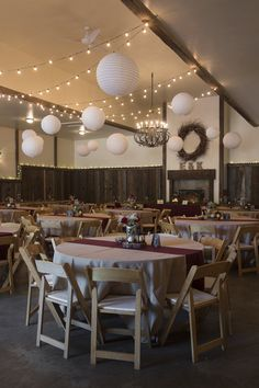 Rustic indoor wedding reception decor - twinkle lights + hanging paper Chinese lanterns with neutral table linens + burgundy table runners {Jessie Moore Photography}