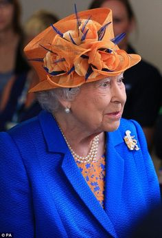 Vibrant: The Queen opted for an electric blue coat, printed dress and orange hat Read more: http://www.dailymail.co.uk/femail/article-4541026/The-Queen-visits-Royal-Manchester-Children-s-Hospital.The Queen visited the hospital in a show of solidarity for the survivors, and those who battled to keep them alive DailyMail