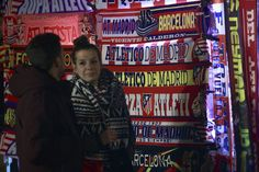 Atletico de Madrid fans look at scarfs displayed at a merchandising stall before the Copa del Rey semi-final first leg match between Club Atletico de Madrid and FC Barcelona at Estadio Vicente Calderon outdoors on February 1, 2017 in Madrid, Spain.