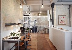 Chevron wood floors, white tiled counter, stainless steel commercial sink, concrete wall, hanging light bulbs