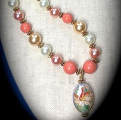 A soft lacy hand-painted lily floats on a glass opal pendant and hangs from an array of coral crystal pearls!  A true Finales exclusive necklace! 18 inches in length.