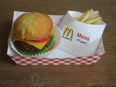 Een originele kindertraktatie: Een snoephamburger met chipsfrietjes. De broodjes zijn gemaakt van een doorgesneden cupcake, de hamburger van een chocoladecake en het beleg van gekleurd marsepein.  voor het zakje friet zijn chips frietjes gebruikt.