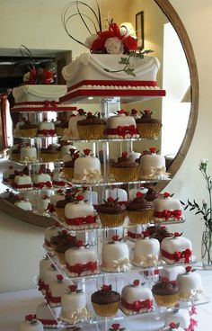 Mini Wedding Cakes and Cup Cake displayed on a 7 tier Acrylic Stand for your Wedding with a top cake for cutting.  Side drapes to the top cake with wired sugar flowers adds elegance to the display