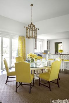 The wife wanted a cheery yellow kitchen, so Paterson covered chairs and stools in sunny Piton vinyl from Prismatek and used Romo's Portico for curtains.