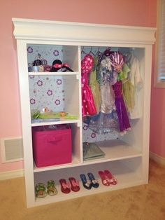 Old entertainment center, doors removed and painted, install rod and voila! Also good for a child's wardrobe.  This would be adorable for a little girl's dress-up stuff!