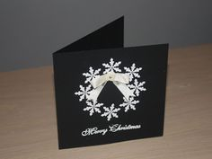 black handmade card ... wreath of punched white snowflakes ... clean and simple ... elegant too ...