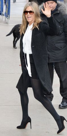 Jennifer Aniston gave a wave on her way to Good Morning America in a white sleeveless Michael Kors neck-tie blouse, a black mini, a fuzzy black topper, Wolford opaque tights, and black pumps.