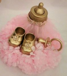 These centerpieces are a perfect addition to any royal celebration! They can be used for a royal baby shower, babys first birthday or princess theme party!  This listing is for a set of 2 Each one is approximately 6 inches tall and 7 inches wide   The base is covered with beautiful carnations. The top is adorned with a pair of golden booties, a golden pacifier and a golden bottle. *** The shade of pink I use in this photo is a light pink color ***    If you have any questions please feel…