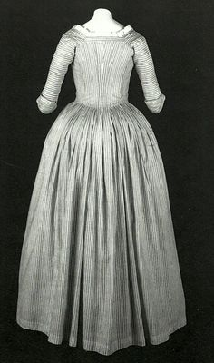 """Closed Gown. Robe à l'Anglaise: ca. 1775-1780. # 1959-113-1. CB. American, striped cotton plain weave. """"This gown is a rare surviving example of the type worn by servants and the lower classes, or by middle class women for informal wear. The plain design and the use of cotton fabric are well suited to an informal dress, but also reflect the growing preference for simplicity during the 1770s and 1780s. At this time, dresses with closed skirts became popular; called """"round gowns,"""""""