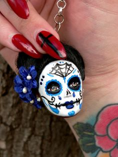 This is a listing for a custom made day of the dead doll keychain. It will include one custom made/hand painted doll head attached to a keychain for all of your sugar skull needs! Just convo me with your preference for doll hair color/ paint design/ and anything else you may have mind for your keychain and I will custom make you one to your liking! Check out our instagram and Facebook for more custom sugar skull examples!  https://www.instagram.com/starosecreatio...