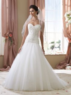 This very pretty white, never worn wedding dress is in pristine condition with original tags. The strapless sweetheart neckline is defined with beaded embellishments. The formfitting bodice is detaile
