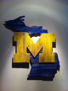 Handcrafted wooden state of Michigan with University of Michigan logo made from pallet wood. Dimensions are approximately 24x27 inches.    The products displayed on this website are not endorsed, sponsored or approved by or affiliated or associated with any individual or entity including without limitation any college or university.    Because each of our pieces is hand cut from wood that can have a rough texture, knots, small cracks or other imperfections that add to its rustic nature…