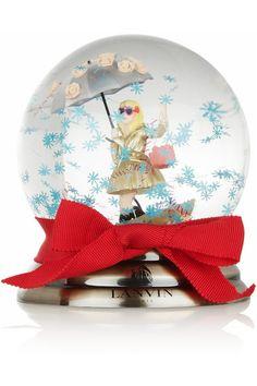 Lanvin propose une version chic de la traditionnelle boule à neige grâce à ce modèle Miss Lanvin présenté dans le coffret bleu emblématique de la marque. Cadeau idéal pour les amoureux de la mode, cette création en verre renferme une poupée en plastique et est rehaussée d'un nœud en gros-grain rouge