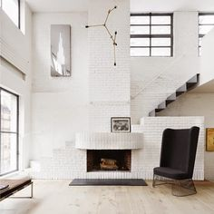 """I really love how the stairs are behind the fireplace. Cool idea! Photo by Thomas Loof. #interiorarchitecture #fireplace #interior #whiteinterior…"""