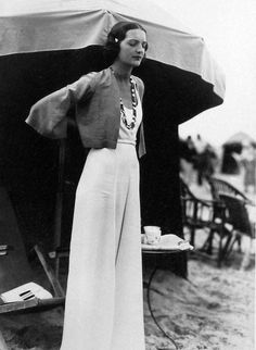 Sleek white, high-waisted trousers worn with white strappy top and bolero jacket, simply accessorised with long beaded necklace and small decorative hair pin. 1930's Fashion - Photo by The Seeberger Brothers