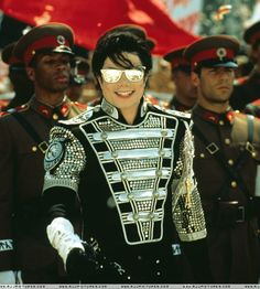 Michael Jackson HIStory era: Black and silver imprints, rhinestones, buttons and buckles with silver armpads. Black jeans and silver shades.