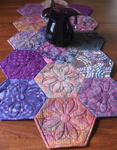 Make this gorgeous hexagon runner using the Hex N More Ruler! Batik fabrics add a pop of color to your table. The IN-R-Form batting alternative gives nice definition to the quilting and the pretty embroidery design, which is free for the month of September, quilts the runner beautifully!