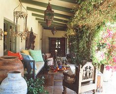 Where do people get porches like this? No fair! I love those Moroccan-y lanterns, the pillows and that chair!