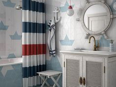 Nautical bathroom featuring white and blue diamond tiles and bold shower curtain. Large ship mirror. Wooden bathroom storage.