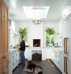 I love everything about this kitchen. Herringbone hardwood, kitchen skylight, kitchen fireplace, marble counters, natural wood doors.