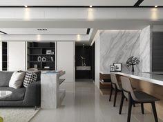 色彩、格局 從玄關入門起始,深、淺跳色,黑白對比的用色,就讓空間層次分明。沿著廊道,步入白色為基調的客廳、書房與餐廳等公共空間,視野豁然開朗。 開放式客、餐廳與書房,以兼具展示、收納機能的低檯度櫃體,形成空間區隔。簡潔俐落的線條,則完美演繹現代風格語彙。 穿越公共區的廊道,則進入私領域。如內玄關的大理石端景,讓房間一分為二,一邊是主臥,另一邊則為更衣間和客房。 材質 運用黑白分明的亮面白色烤漆與深色木紋櫃體,及如水墨畫暈染效果的大理石客廳電視牆與餐廳主牆相輝映,中性色調,柔化了原本剛性的對比色,經由不同材質的自然肌理表現,豐富空間表情。 機能 除了格局動線的巧妙安排之外,住宅設計的生活機能也不容忽略。玄關延伸至客廳的大容量白色烤漆櫃體,以懸空的設計讓量體變輕盈;電視牆下方輕薄得幾乎感覺不到存在的鐵件層板,則具承重考量,下方溫潤的木質抽屜,滿足了收納機能。 書房展示、收納櫃以線性切割手法呼應現代風格,透光的玉石把手則隱含小夜燈的照明機能;沿窗增設的臥榻設計,延續懸空的輕盈化視覺效果。機能隨形的設計創意,無處不在,既滿足生活實用性,同時兼顧視覺美感。