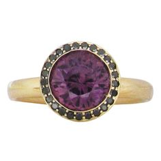 PURPLE SAPPHIRE & BLACK DIAMOND HALO RING A round cut purple sapphire is bezel set into a 14 karat yellow gold petal cut out ring. Surrounding the purple sapphire is a halo of black diamonds. This ring is a size which can also be sized. Gemstone Engagement Rings, Gemstone Rings, Purple Sapphire, Black Diamonds, Halo Rings, Gemstone Colors, Halo Diamond, Fine Jewelry, Wedding Rings
